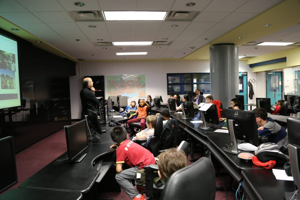 Professor discusses with class in computer lab
