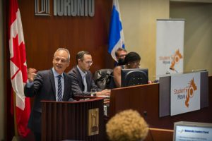 President Meric Gertler gestures while speaking at podium, Canadian flag and StudentMoveTO logo.