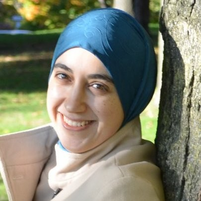 Dr. Eman Hammad outside, leaning against tree trunk
