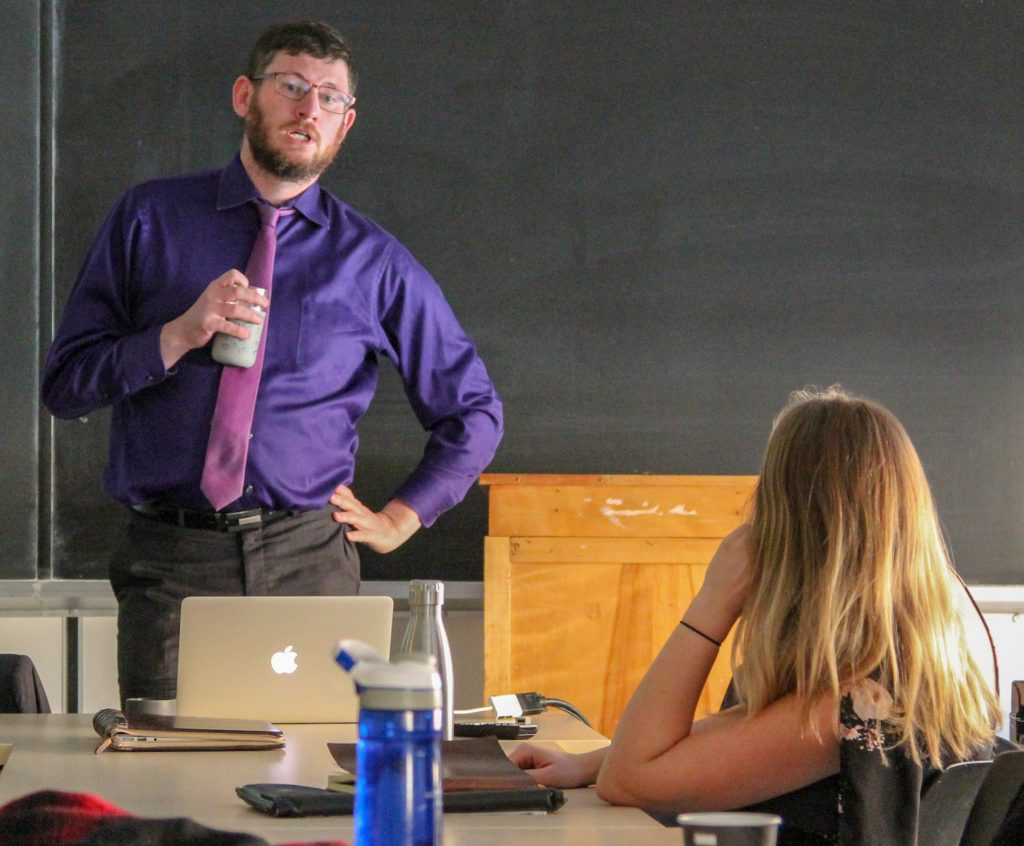 Standing professor answering seated student question
