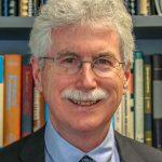 professor standing in front of colourful bookshelves