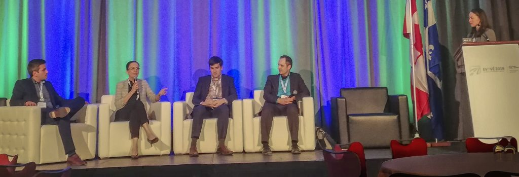 seated panel of four with moderator at podium