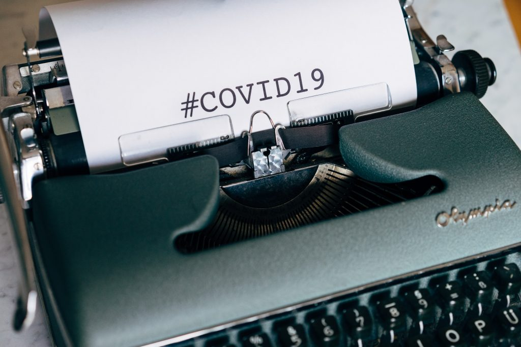 manual typewriter with #COVID19 typed on white paper
