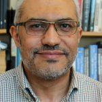 head shot of professor in front of bookshelves